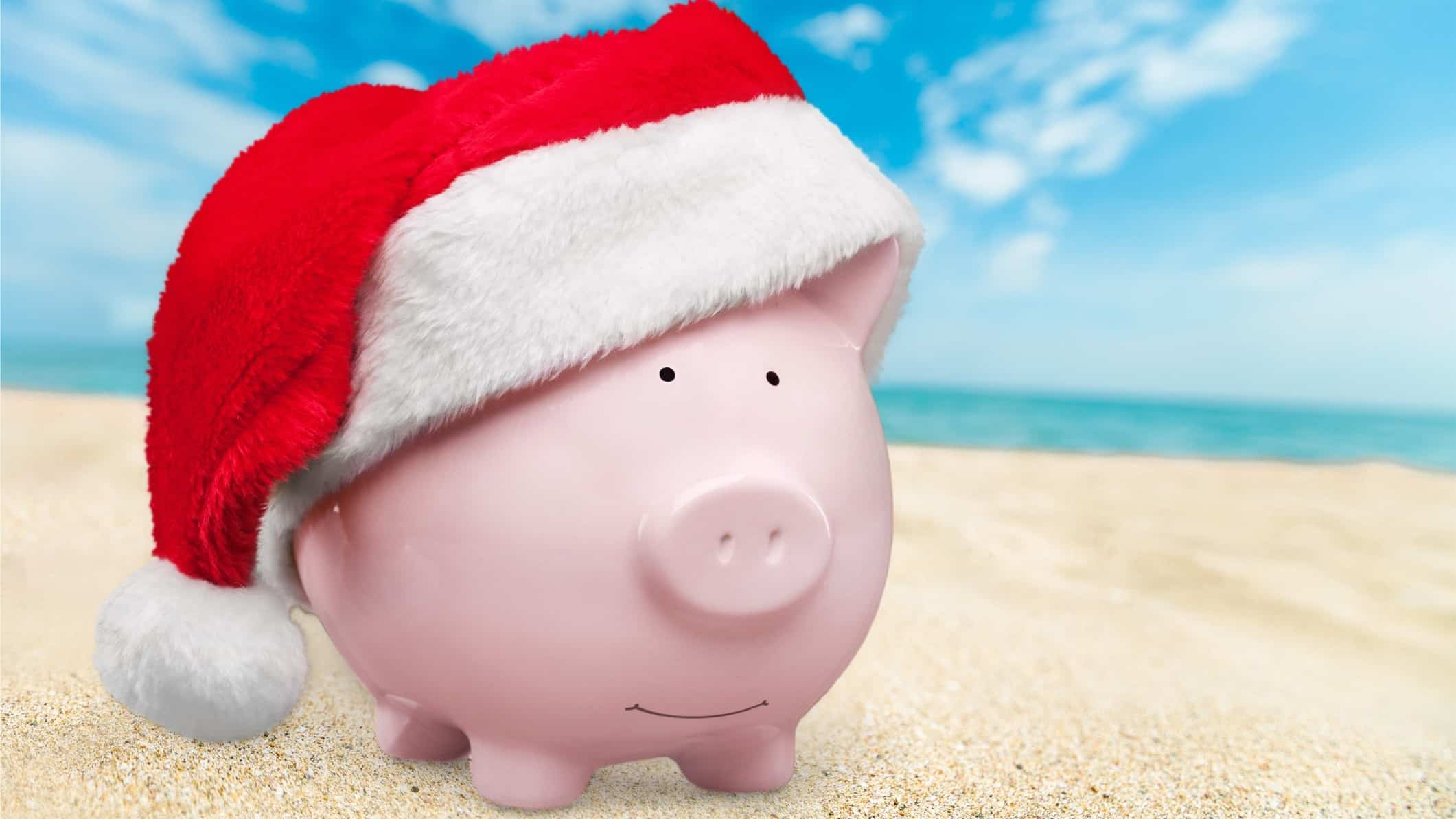 piggy bank sitting on beach wearing christmas hat and representing asx share