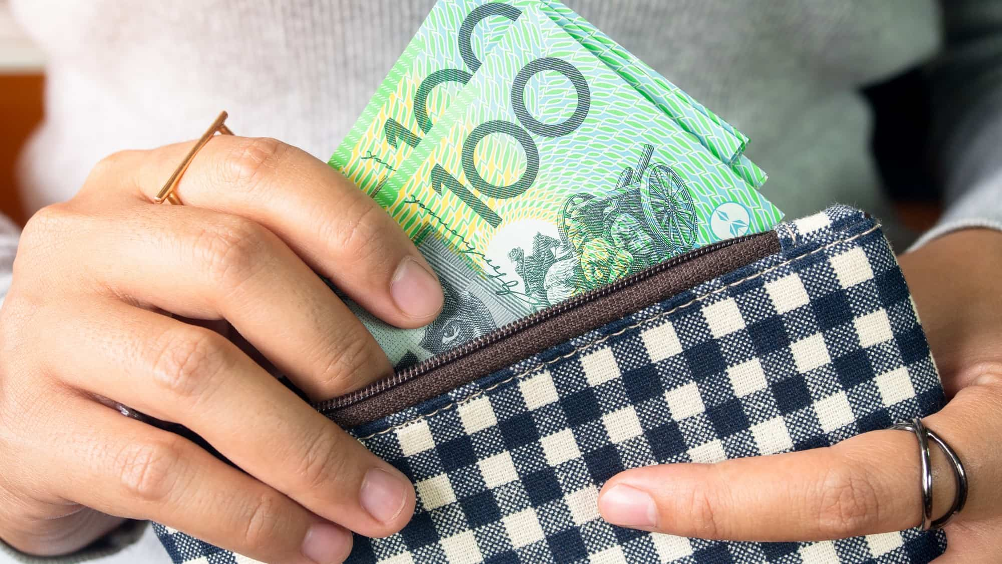woman putting hundred dollar notes into purse