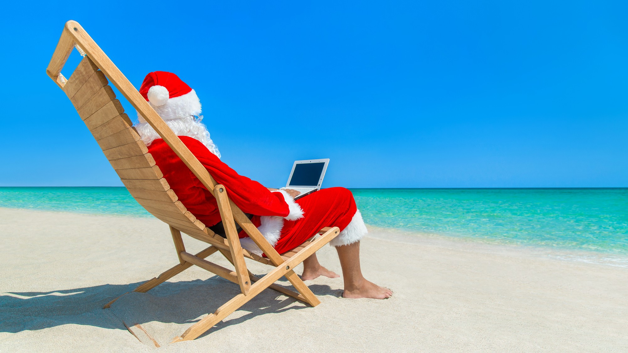 santa sitting on beach looking up best asx shares to buy in december on laptop