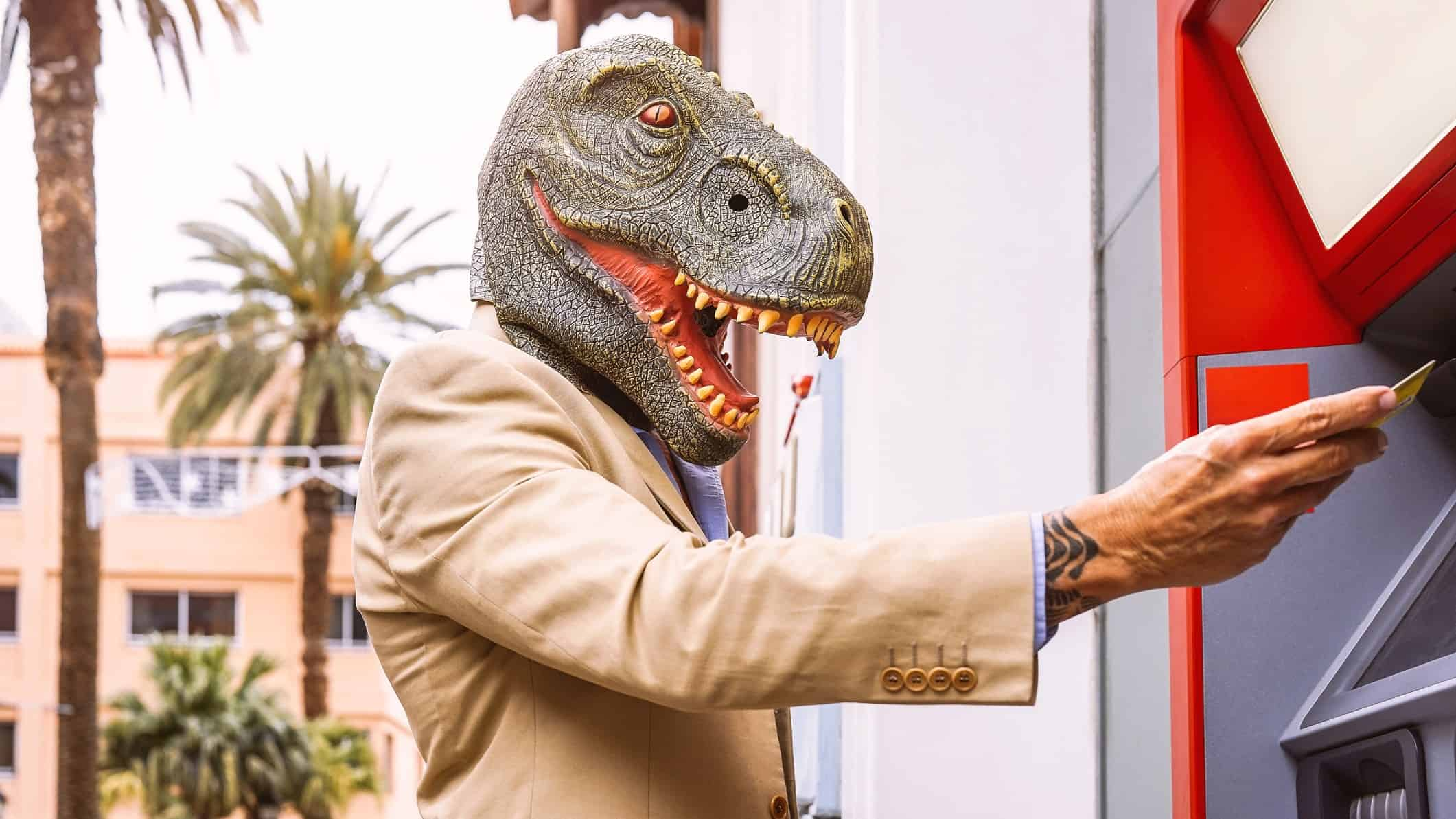 asx shares versus cash represented by man in dinosaur mask withdrawing cash from atm
