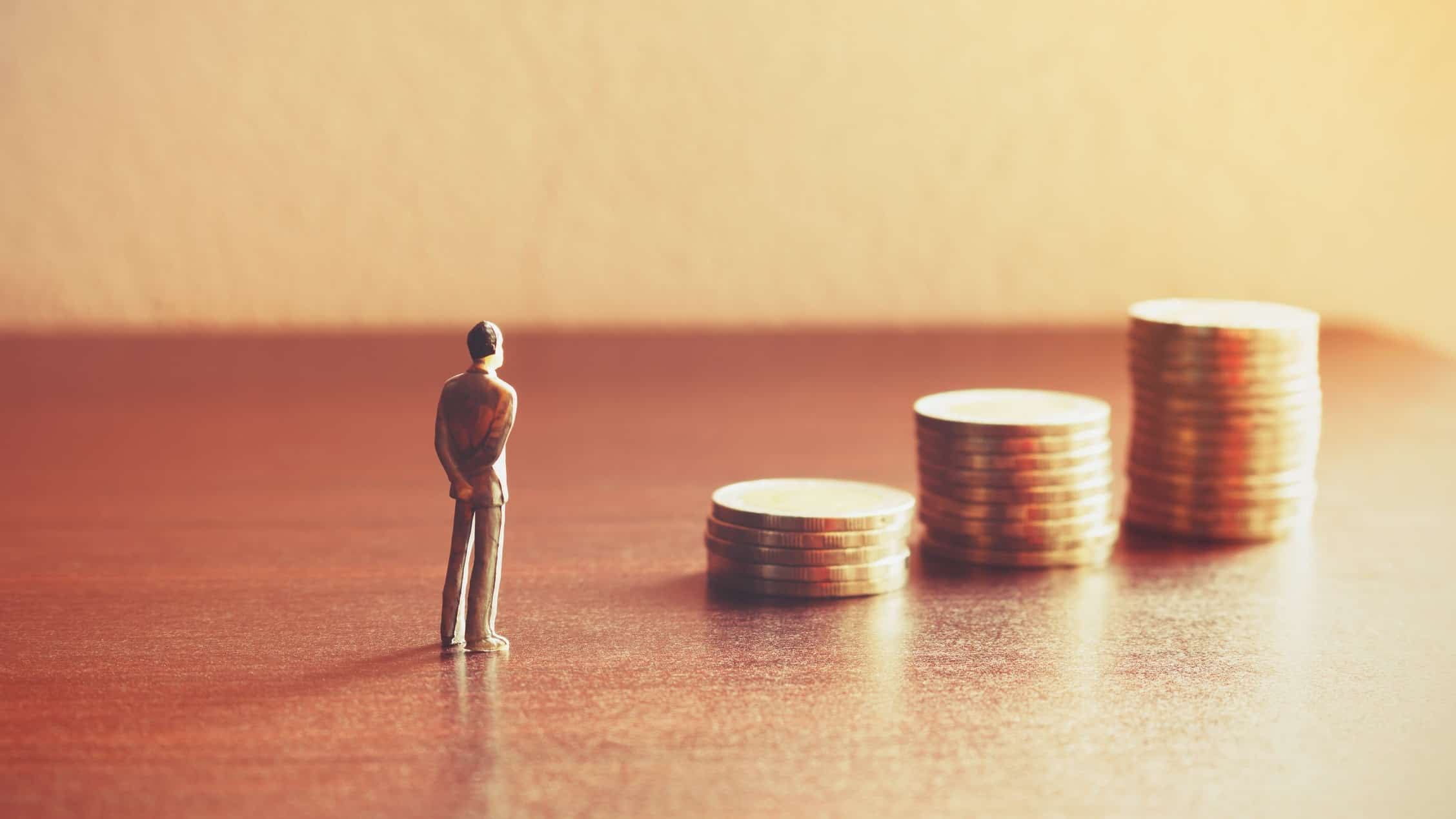 miniature figure of man standing in front of piles of coins