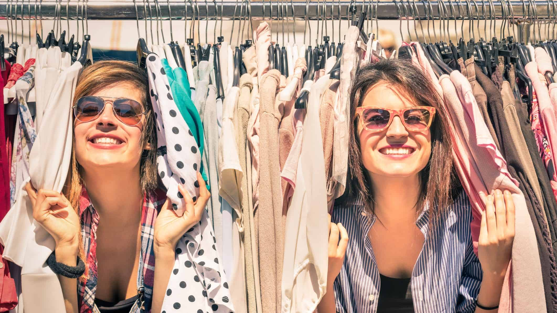 two ladies playing amongst clothes on a store rack