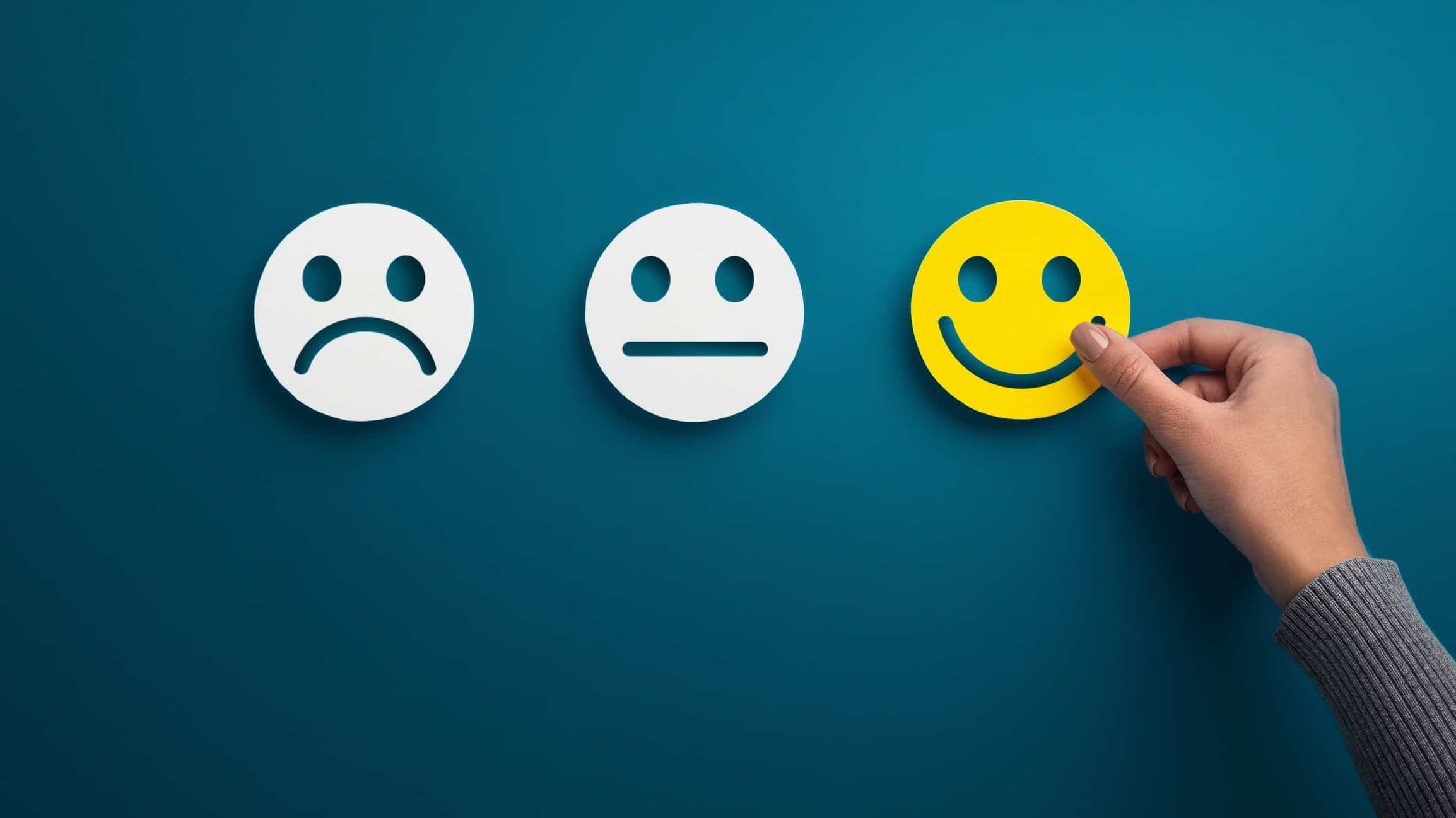 hand selecting happy face from choice of happy, sad and neutral signifying best ASX shares