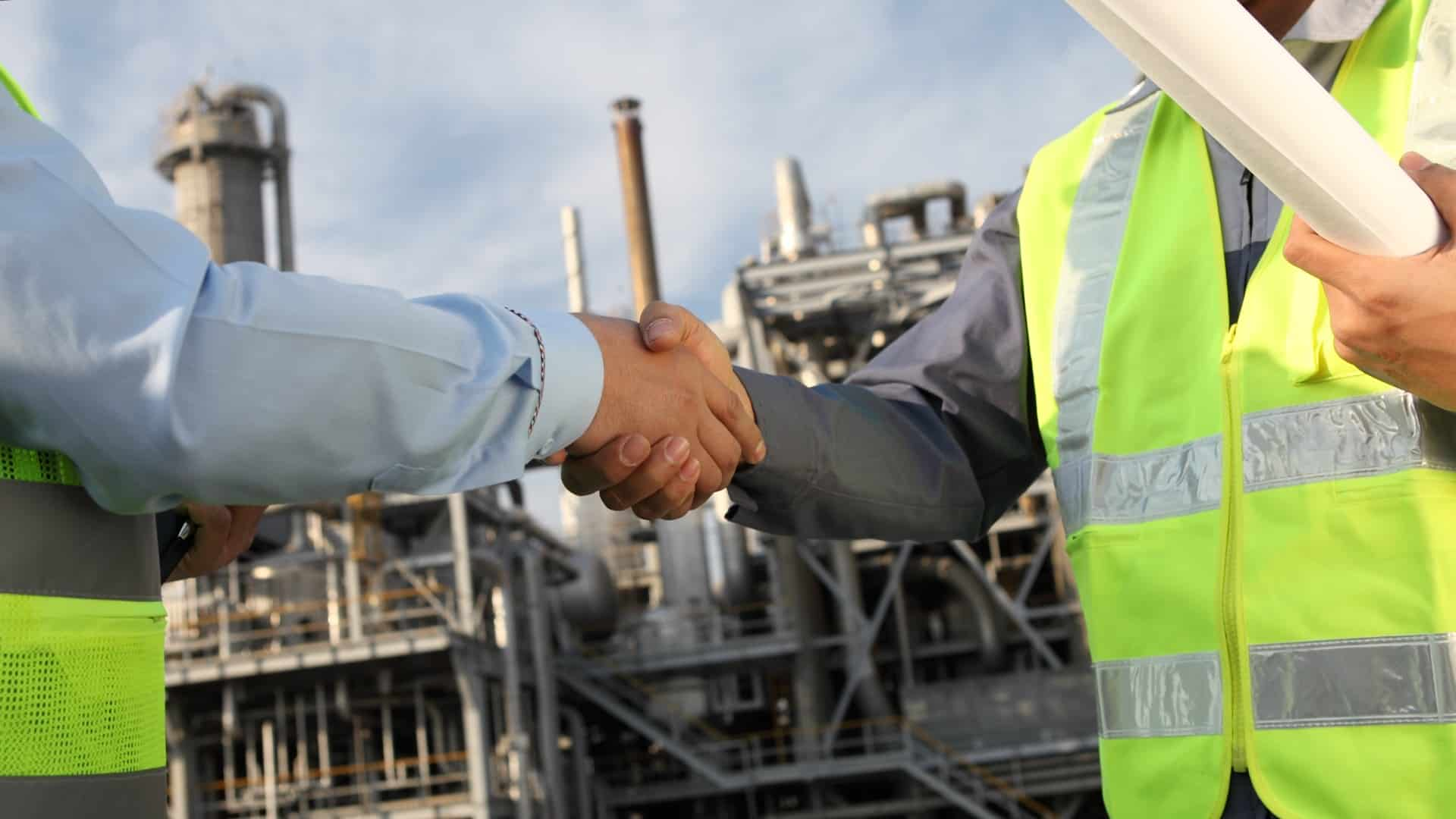 two miners on site shaking hands representing bhp share price