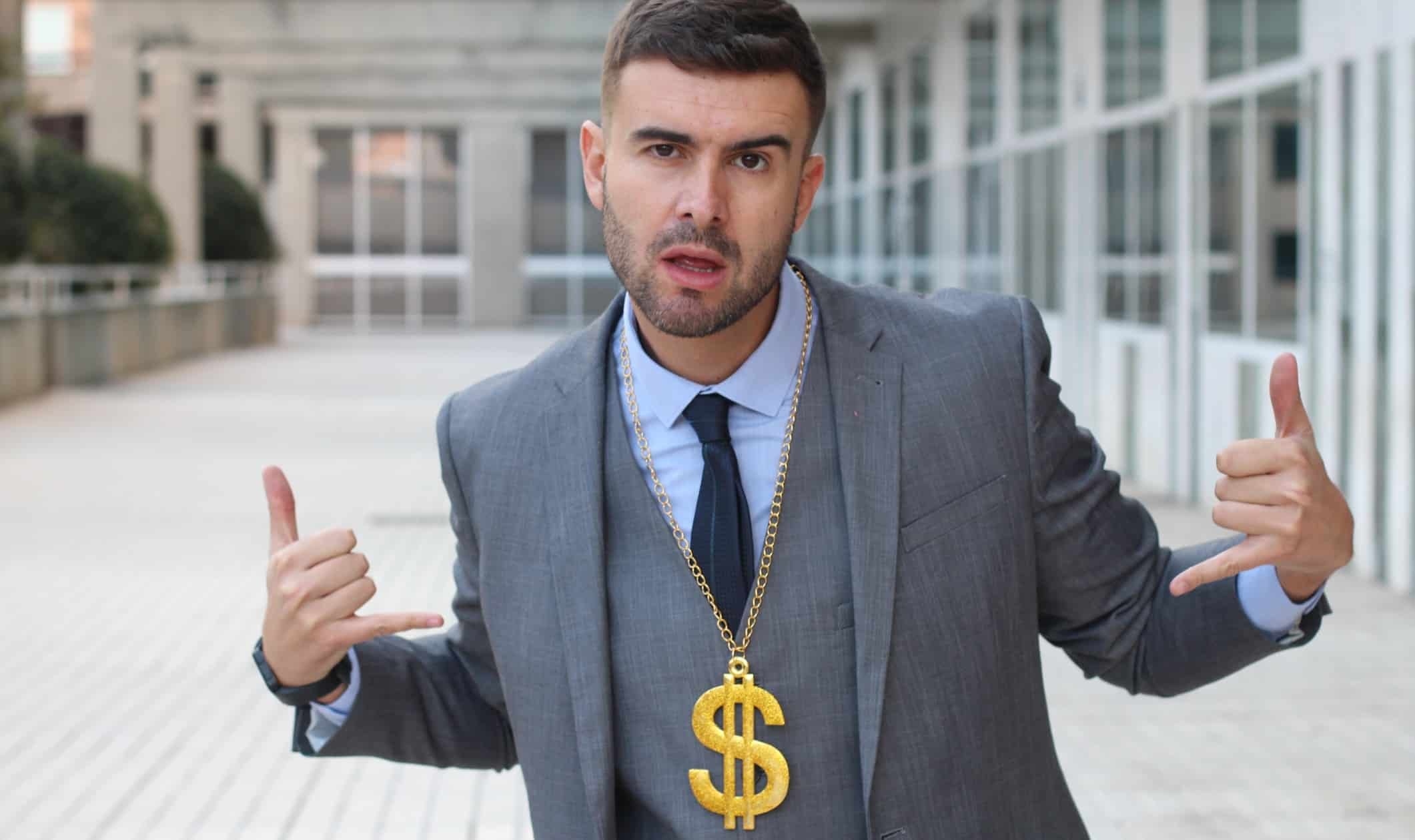 Man in suit with gold chain and attitude happy about making share price gains