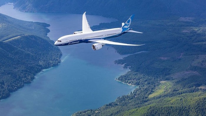 A plane flying over a lake made by Boeing