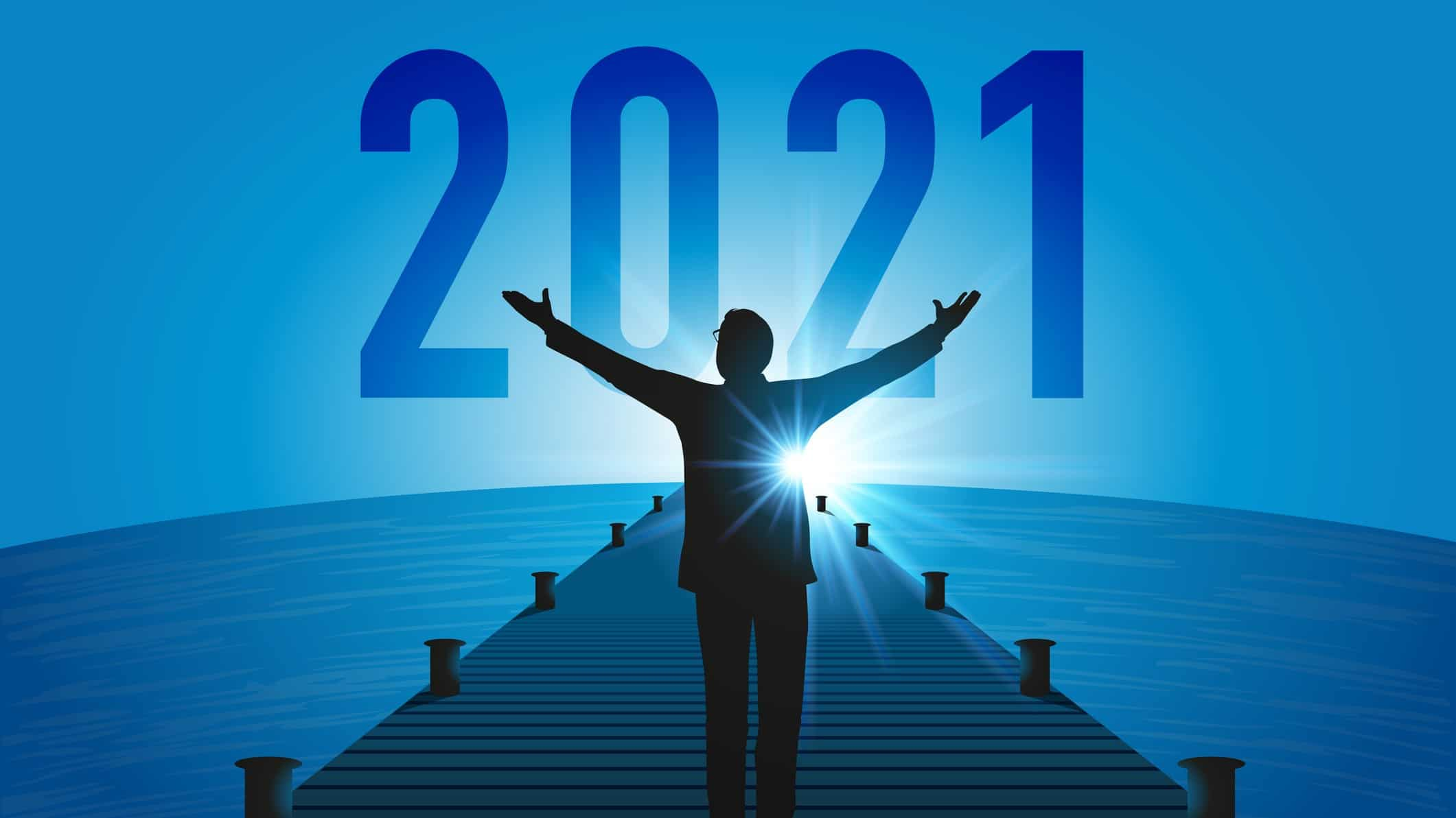 a man raise his arms to the sun as it rises with the year 2021 in the background, indicating a bright future on the ASX share market
