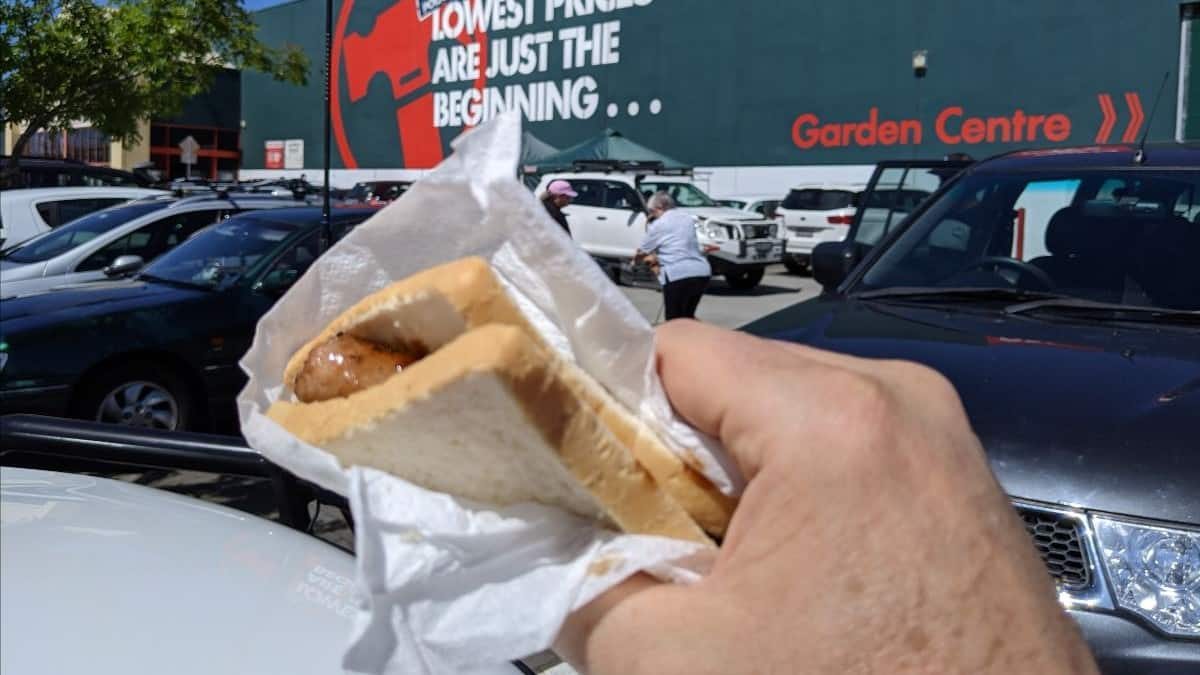 Bunnings stock represented by hand holding a sausage in bread against backdrop of Bunnings store