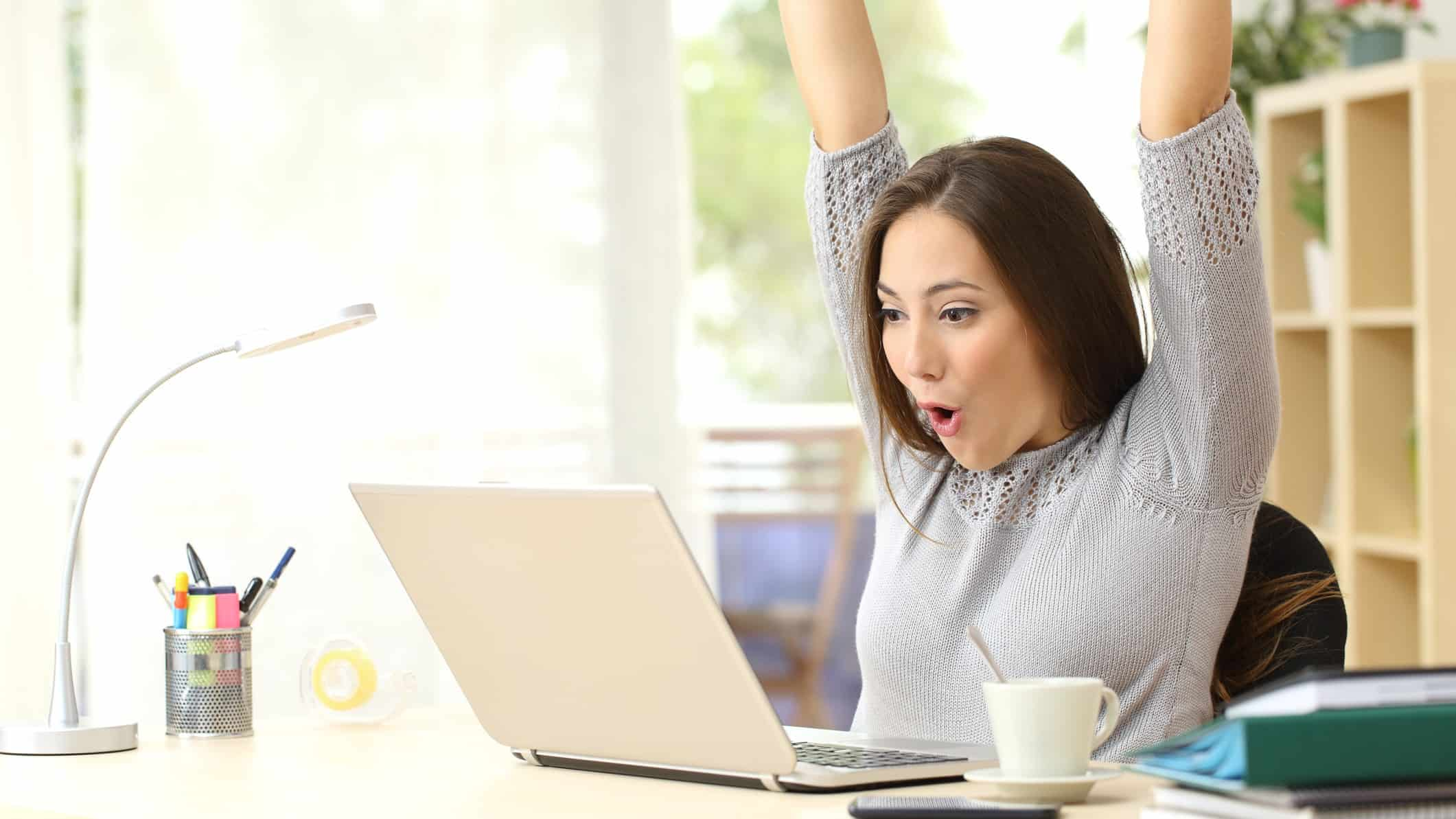 woman throwing arms up in celebration whilst looking at asx share price rise on laptop computer