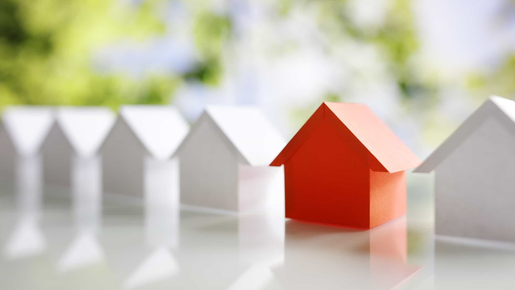 asx shares for housing boom represented by row of miniature white paper houses with one red house