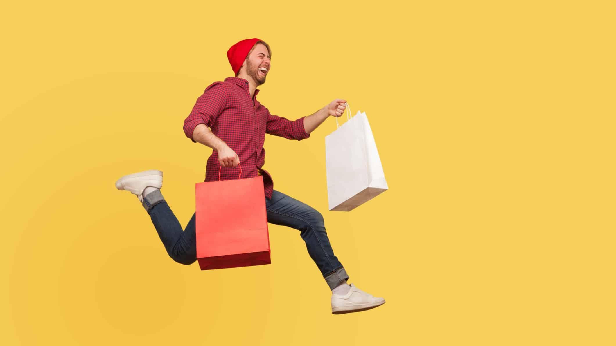 man jumping for joy carrying shopping bags