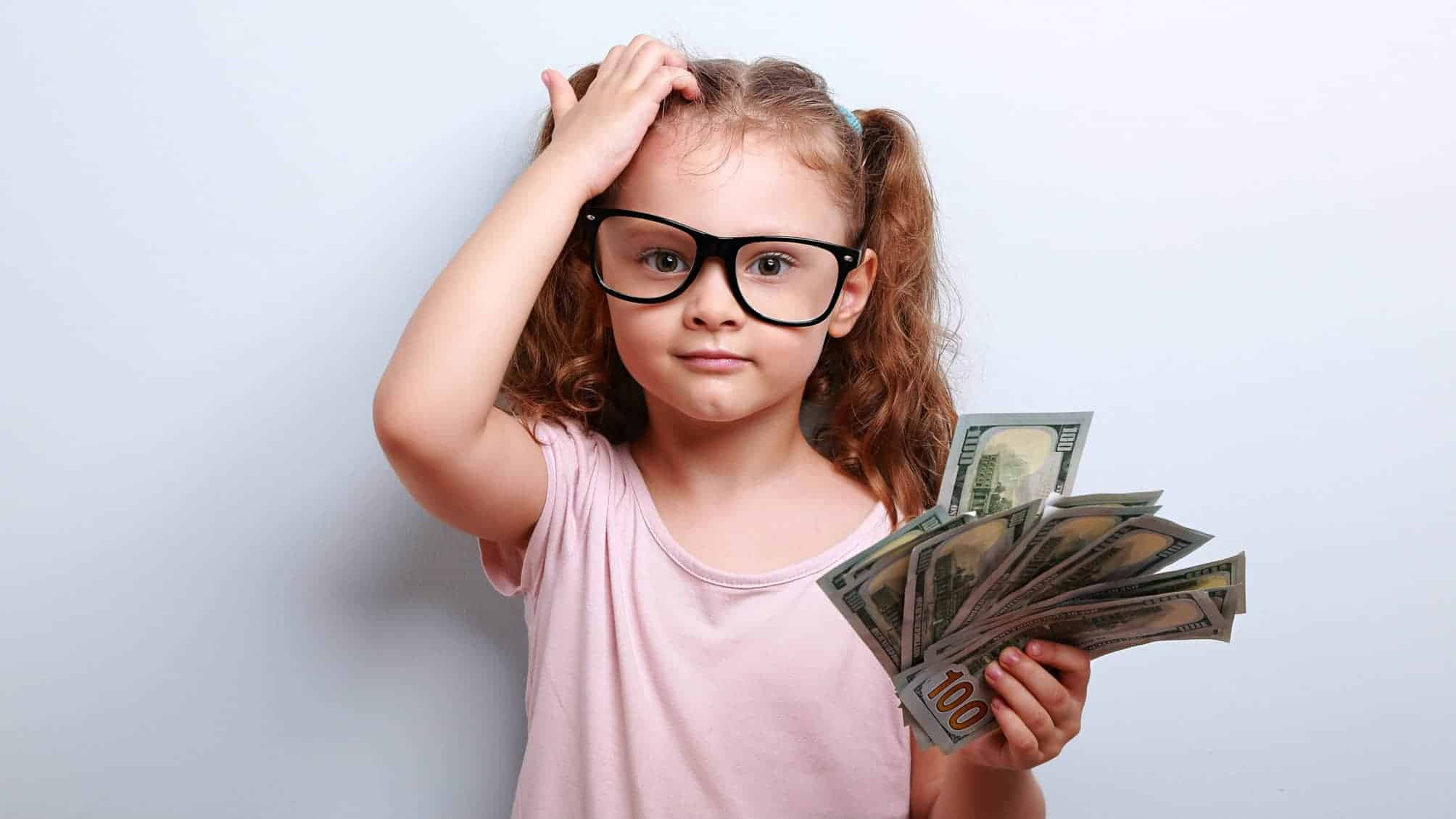 Child holding cash and scratching head