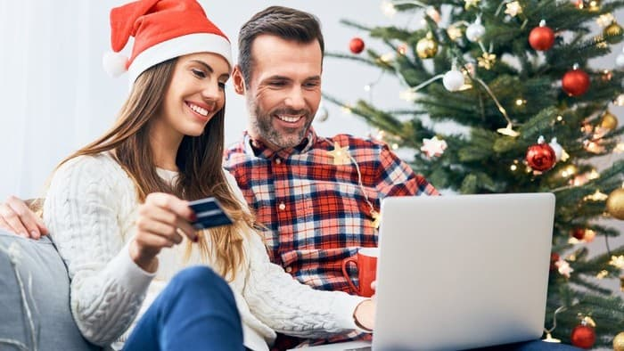 A happy man and woman on a computer at Christmas, indicating a positive trend for retail shares
