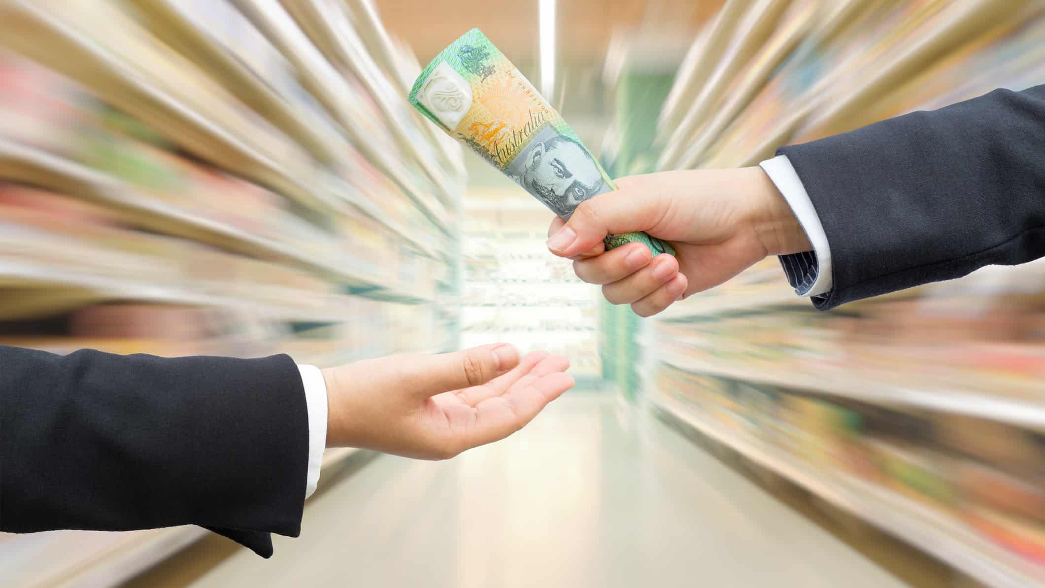 businessman handing $100 note to another in supermarket aisle representing woolworths share price