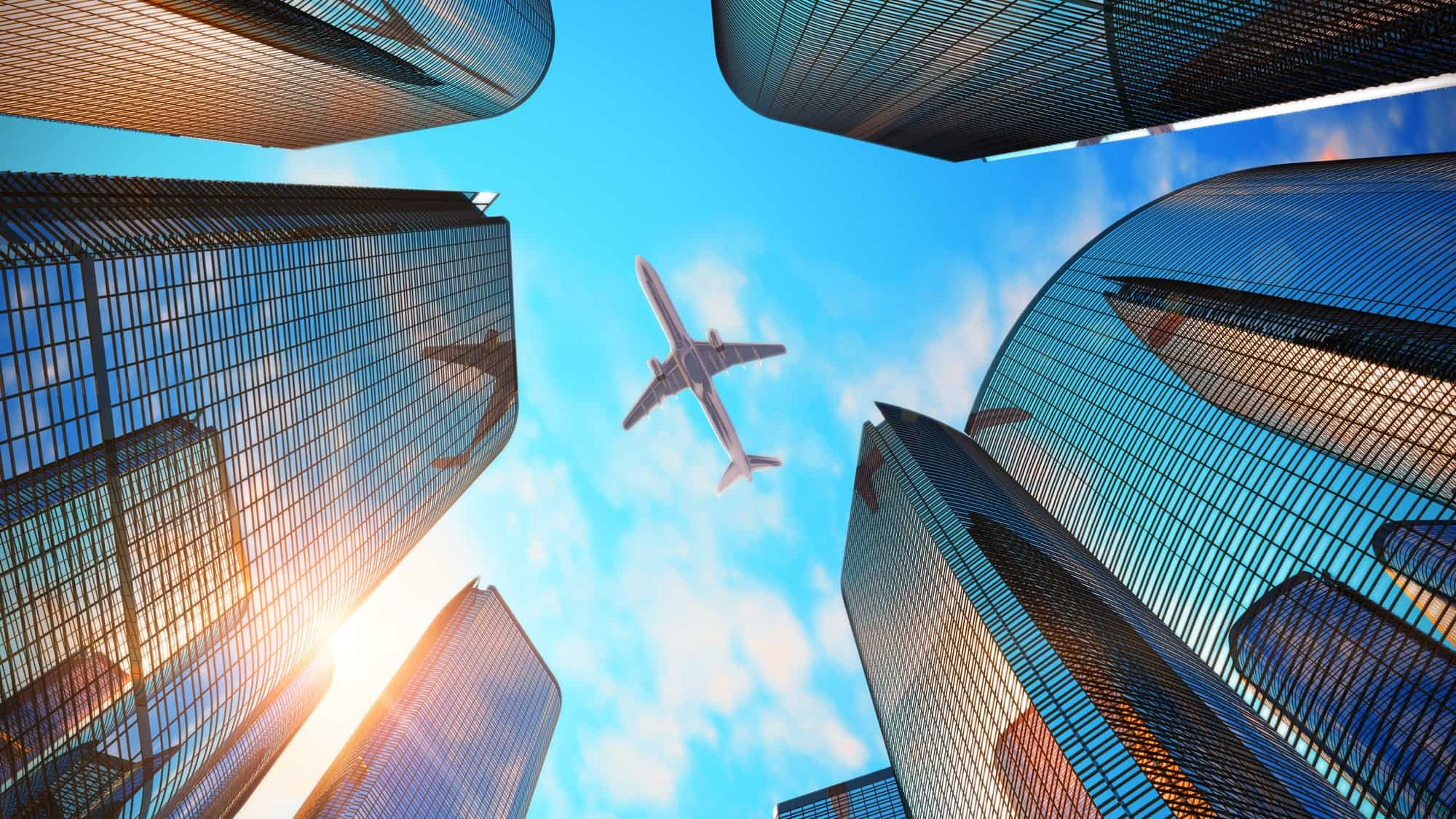 view from below of jet plane flying above city buildings representing corporate travel share price