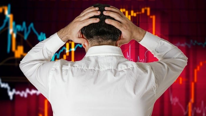 Man in front of chart holding his head as share market crashes