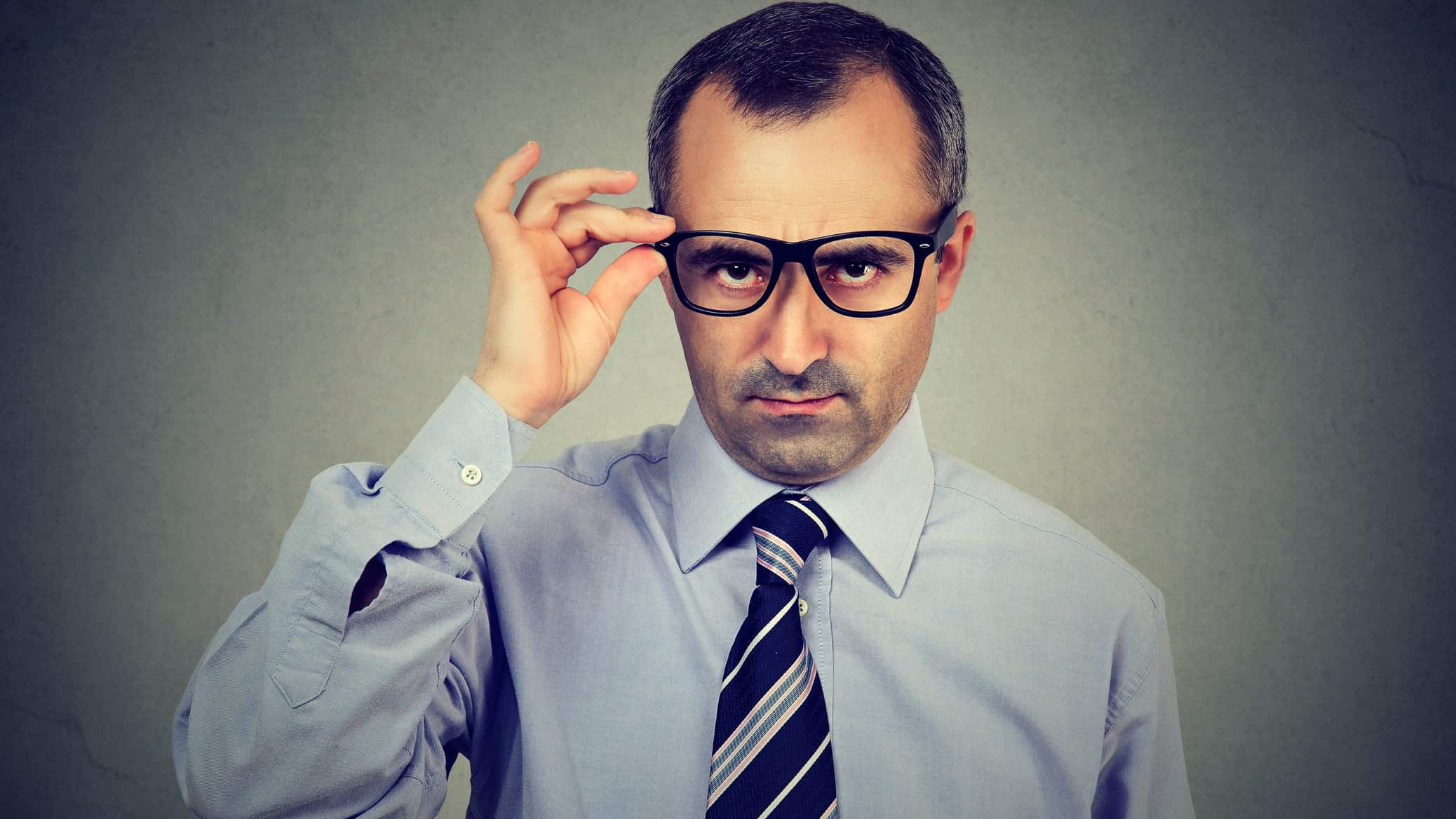 Unimpressed businessman looks down his glasses, indicating an unhappy and critical investor