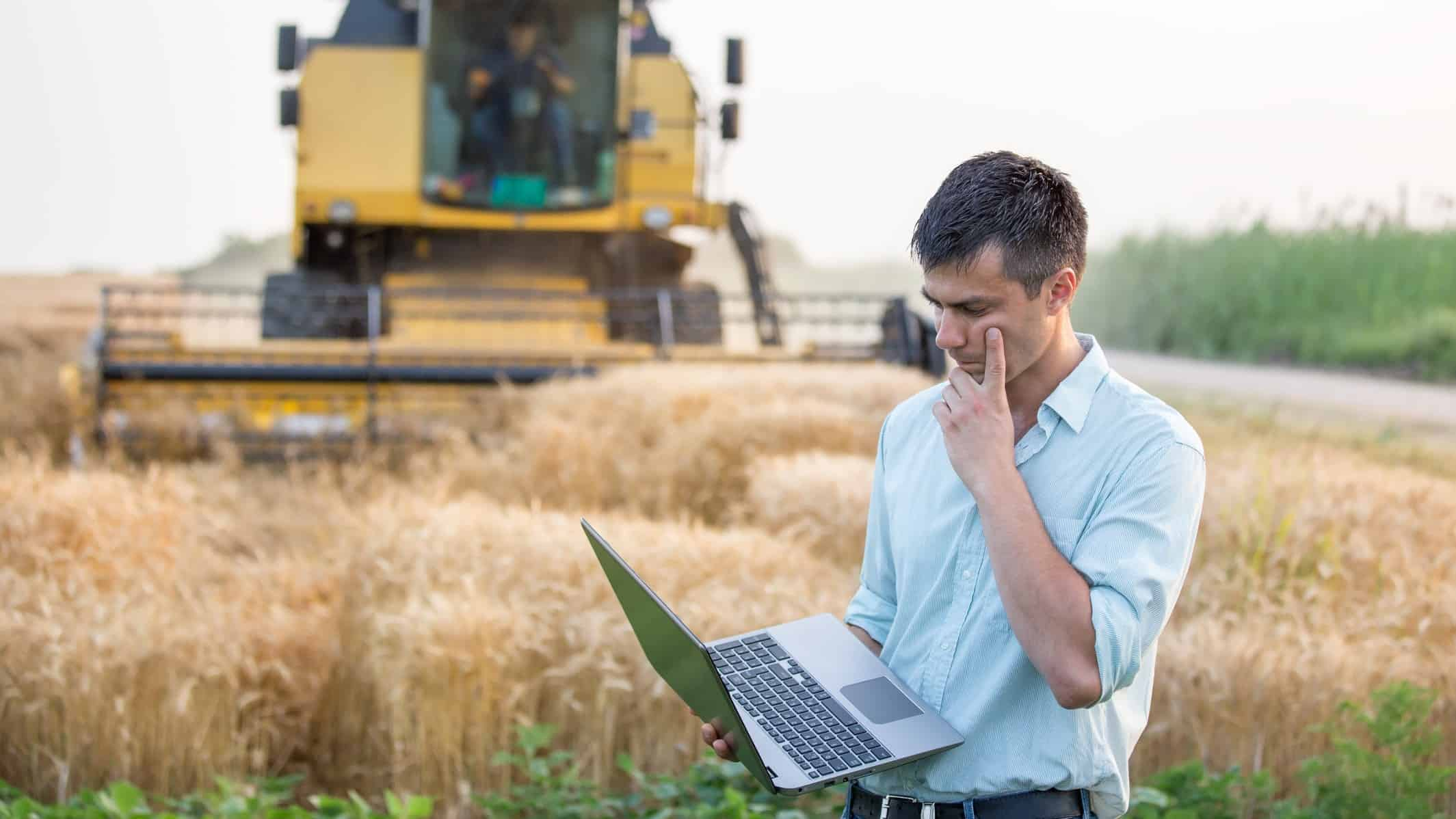 worried famer looks at his computer in front of a harvester, indicating poor prices on the share market