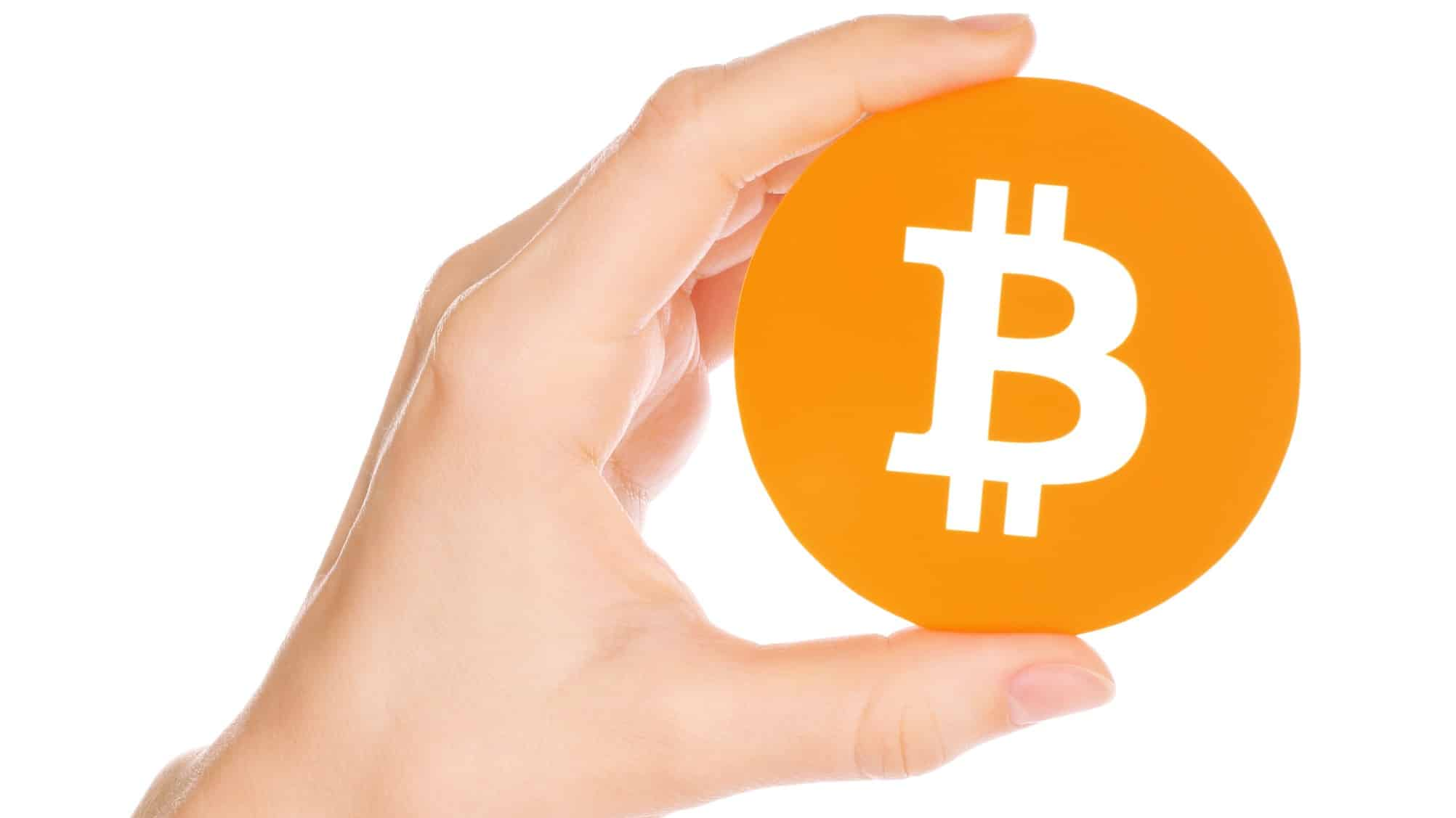 big orange cryptocurrency bitcoin being held up by hand
