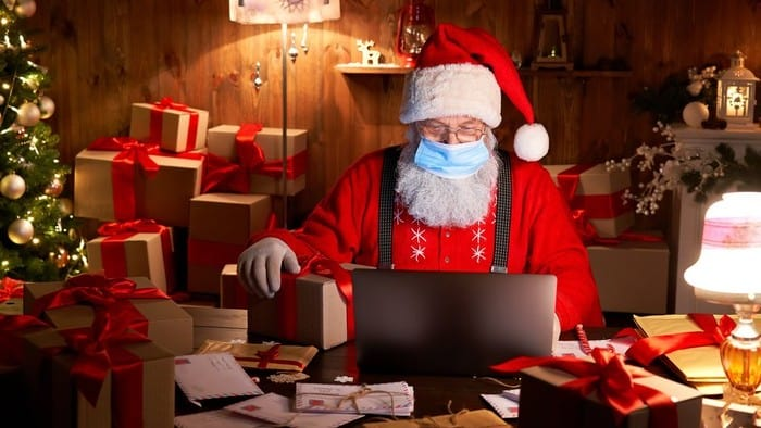 ecommerce asx shares represented by santa doing online shopping on laptop