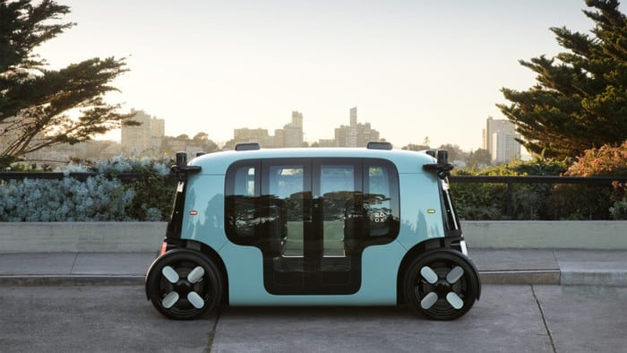 Zoox electric vehicle parked against city scape
