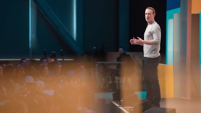 Facebook stock represented by facebook founder Mark Zuckerberg giving speech on stage