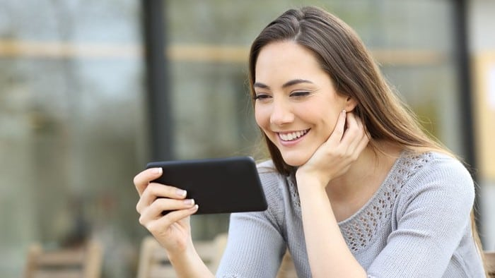 woman looking at facebook on mobile phone