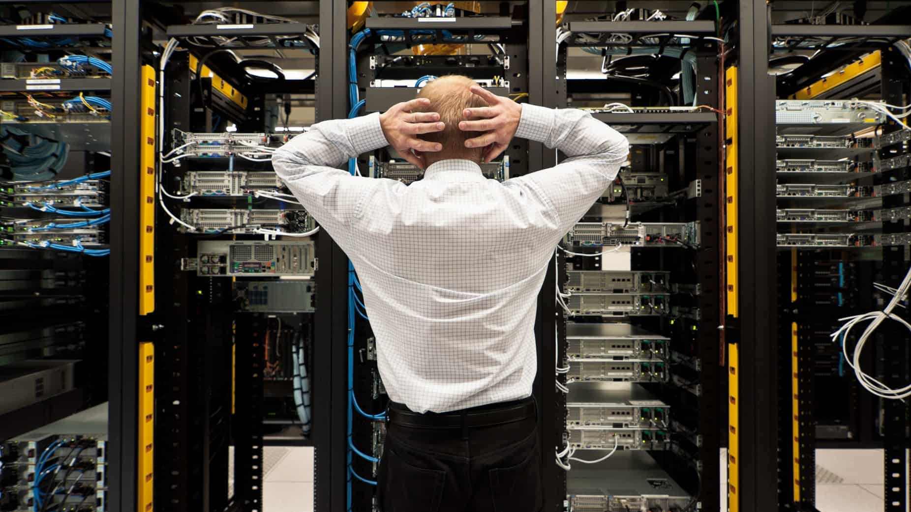 A stressed man with his hands on head trying to work out a major systems failure
