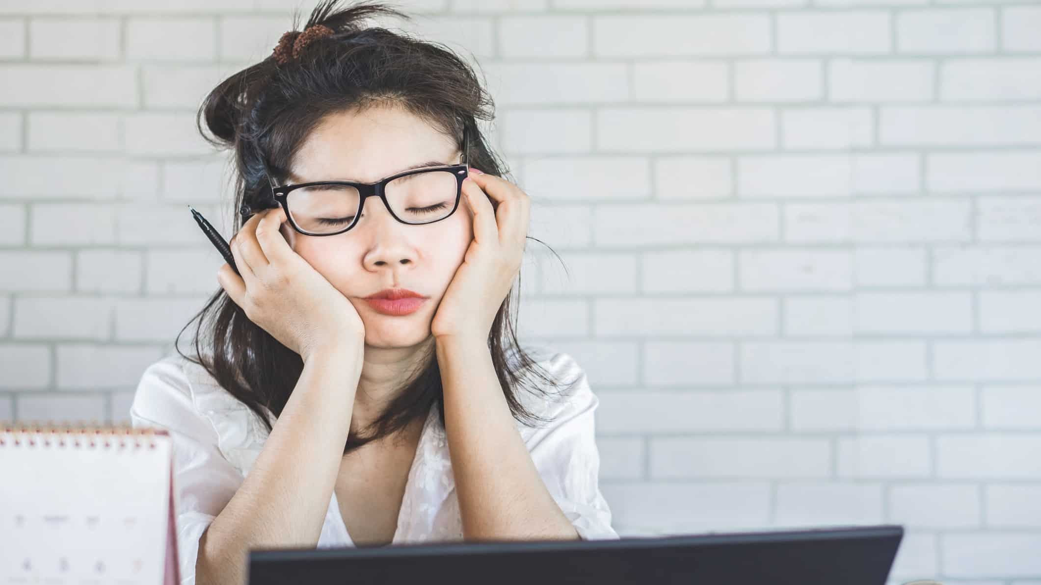 falling asx share price represented by girl falling asleep at her computer