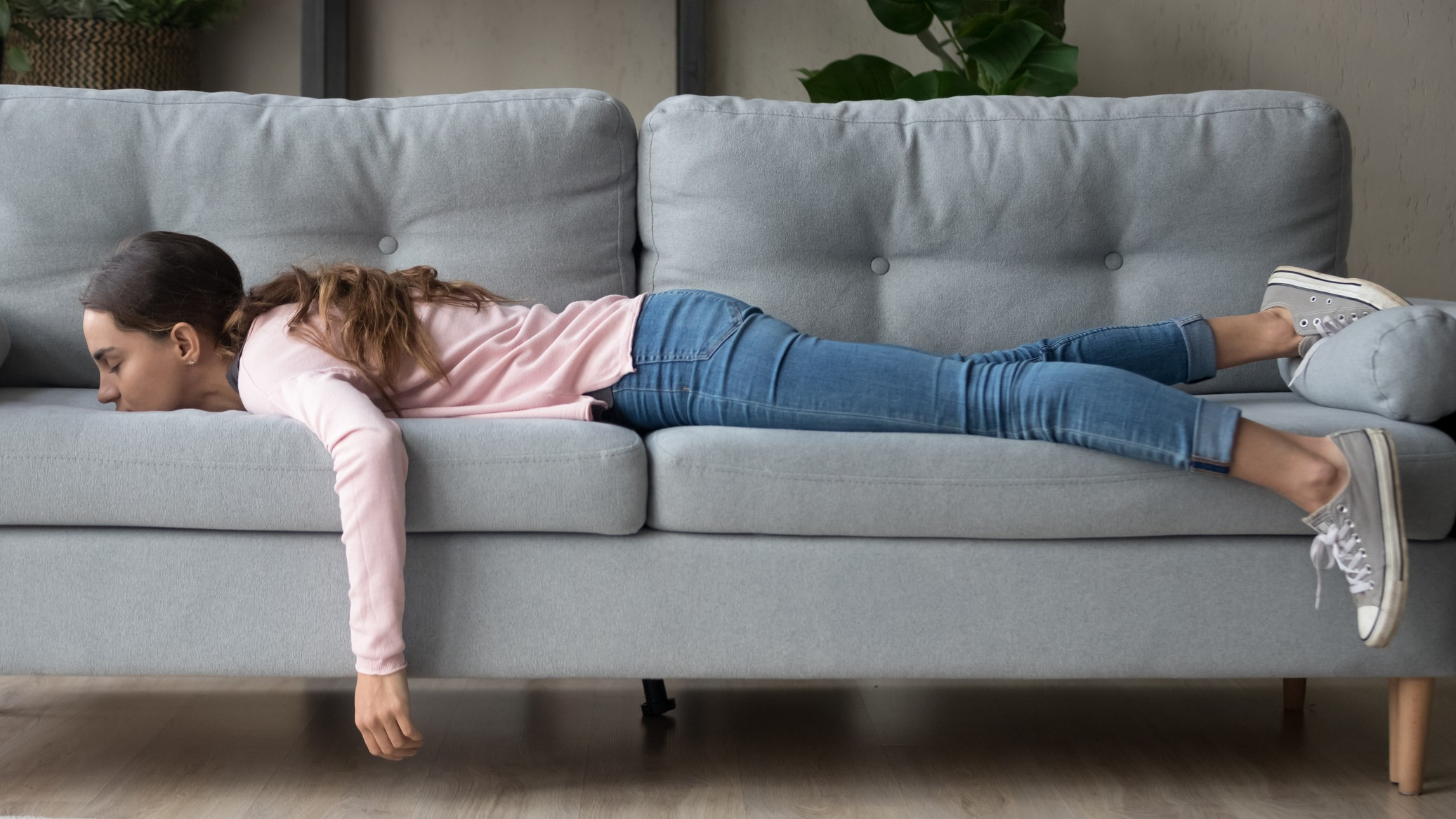 A woman lying face down on the couch, indicating a flat ASX share price