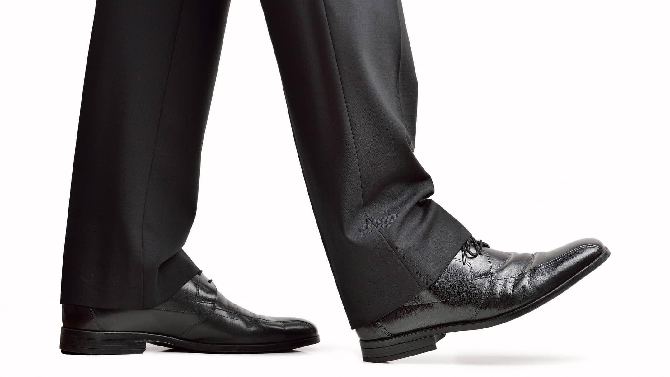 follow warren buffett when buying asx shares represented by business man's legs walking along