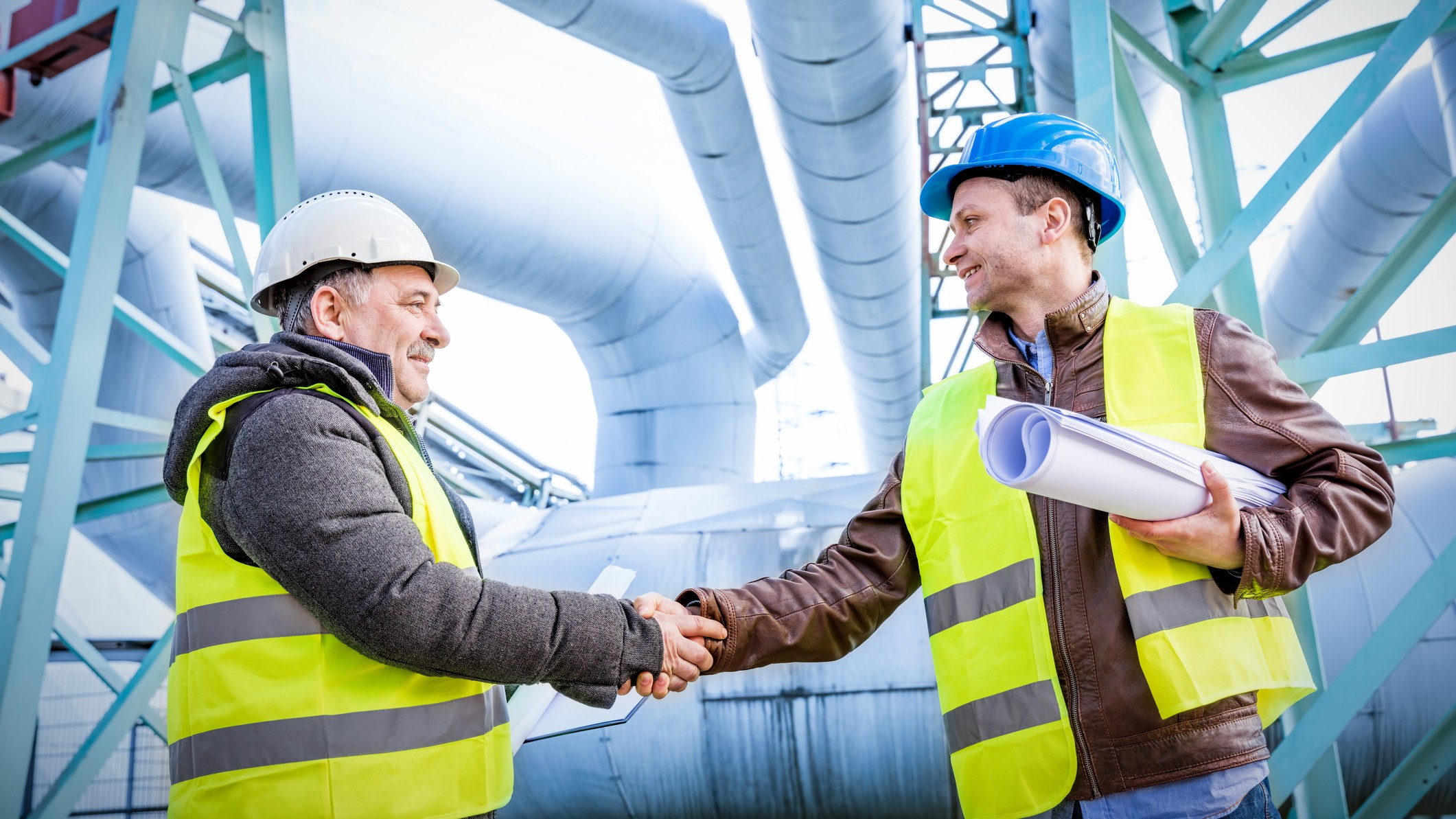 two men in mining hats shake hands on a deal with gas pipelines in the background, indicating good news for the gas and LPG share price