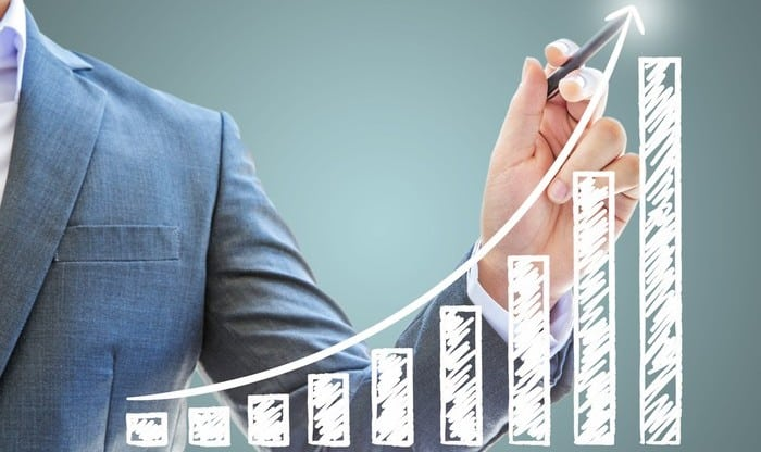 A man drawing an arrow on a growth chart, indicating a surging share price