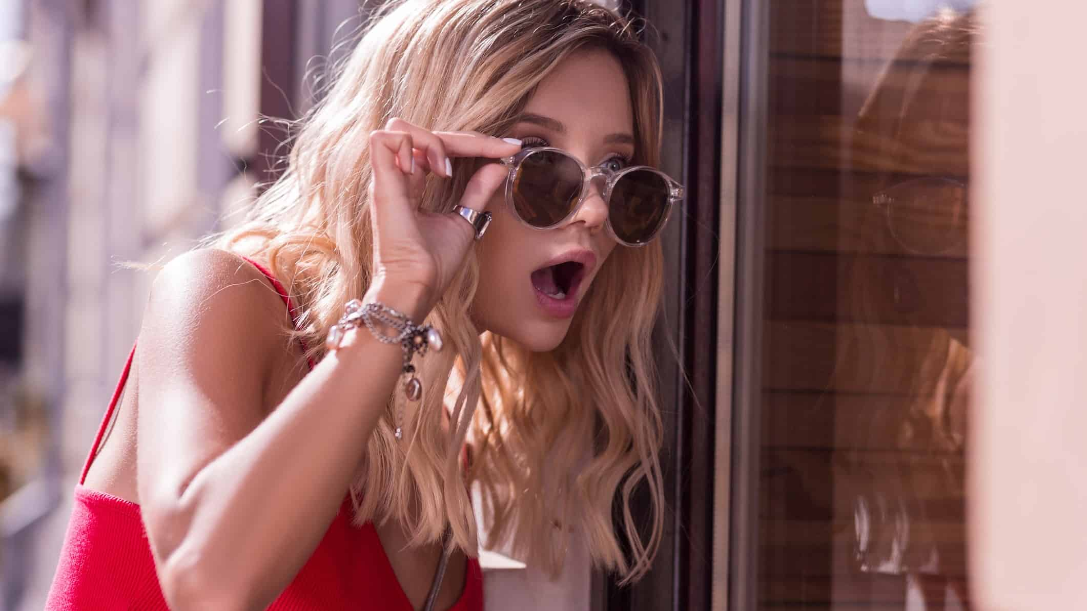 A young woman wearing a silver bracelet raises her sunglasses in amazement, indicating positive share price movement in jewellery shares