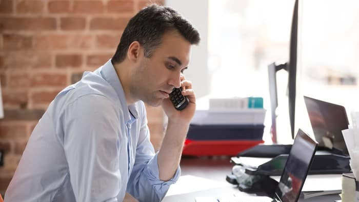 business man sitting and talking on phone whilst investing in asx shares