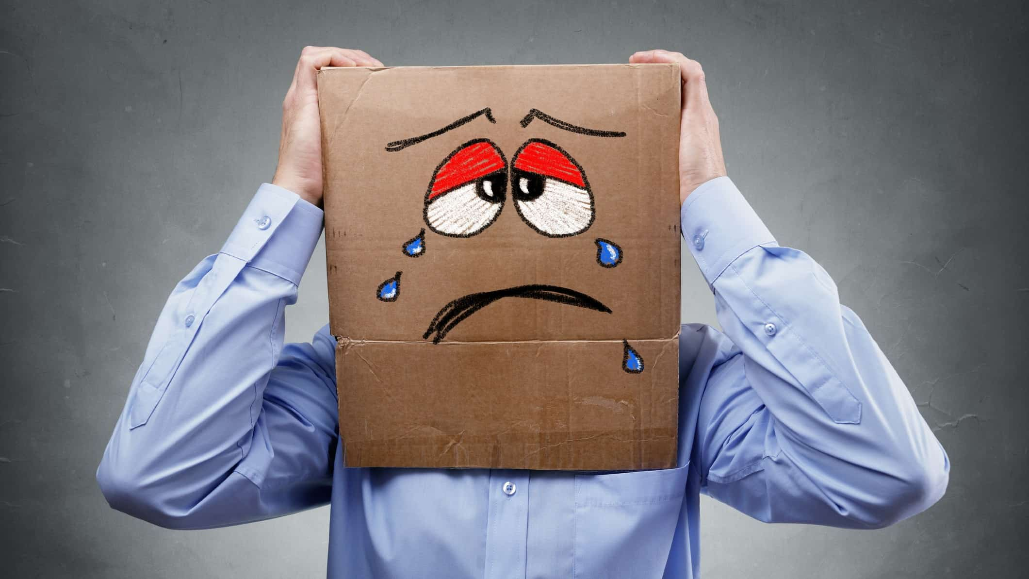 business man wearing box on his head with a sad, crying face on it representing bad investment in asx shares and fall in asx share price