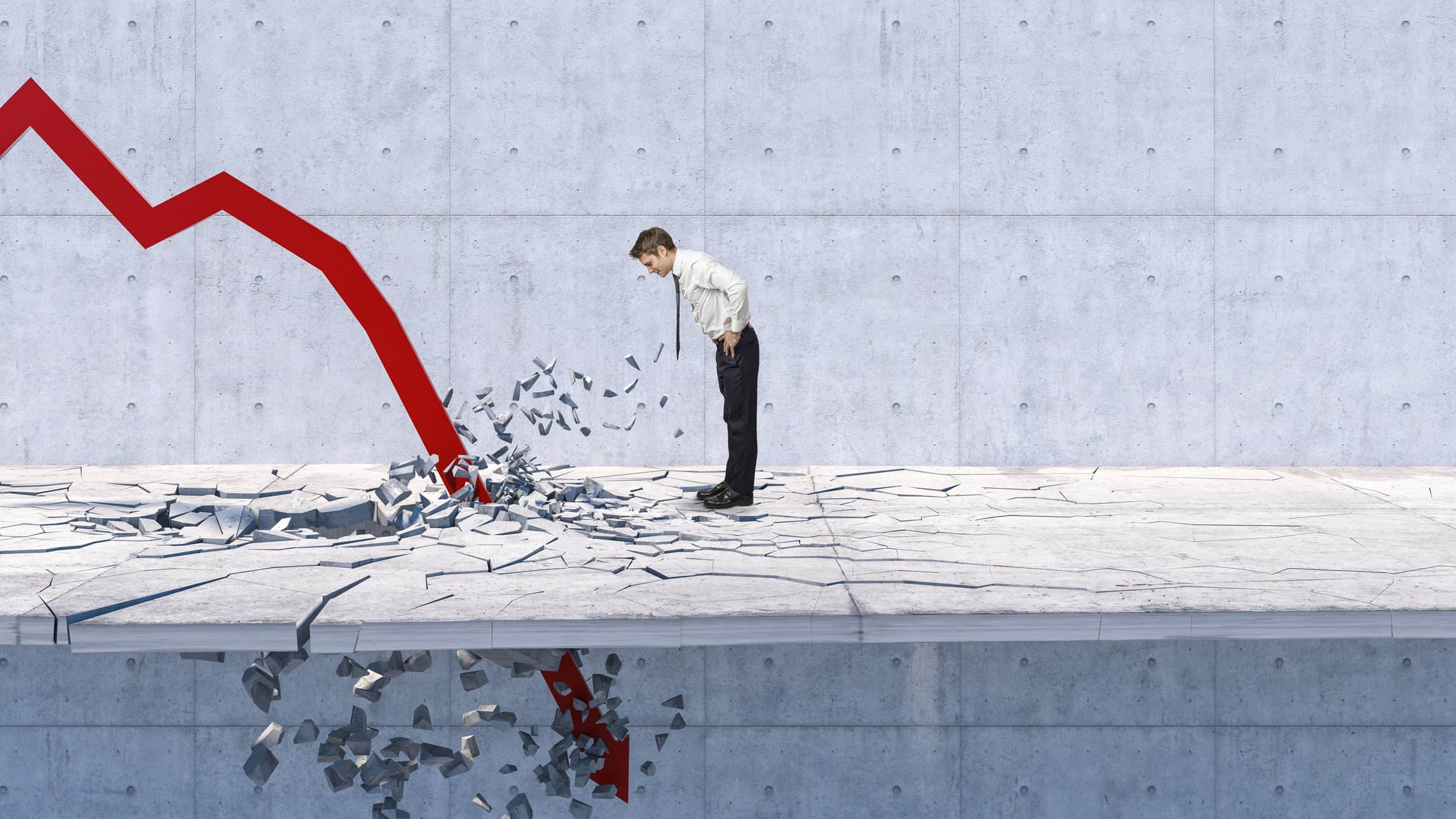 man bending over to look at red arrow crashing down through the ground