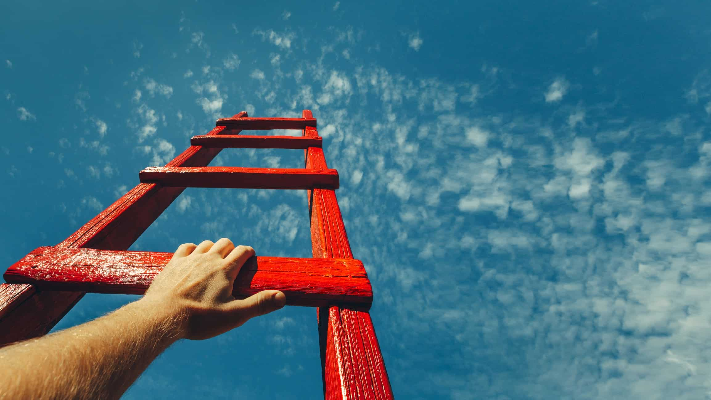 ASX share price rise represented by man's hand grabbing onto red ladder that is pointed towards sky