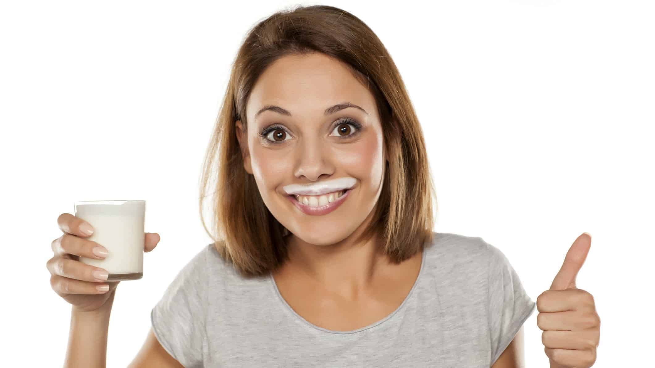 woman with milk moustache holding glass of milk and giving thumbs up representing a positive share price