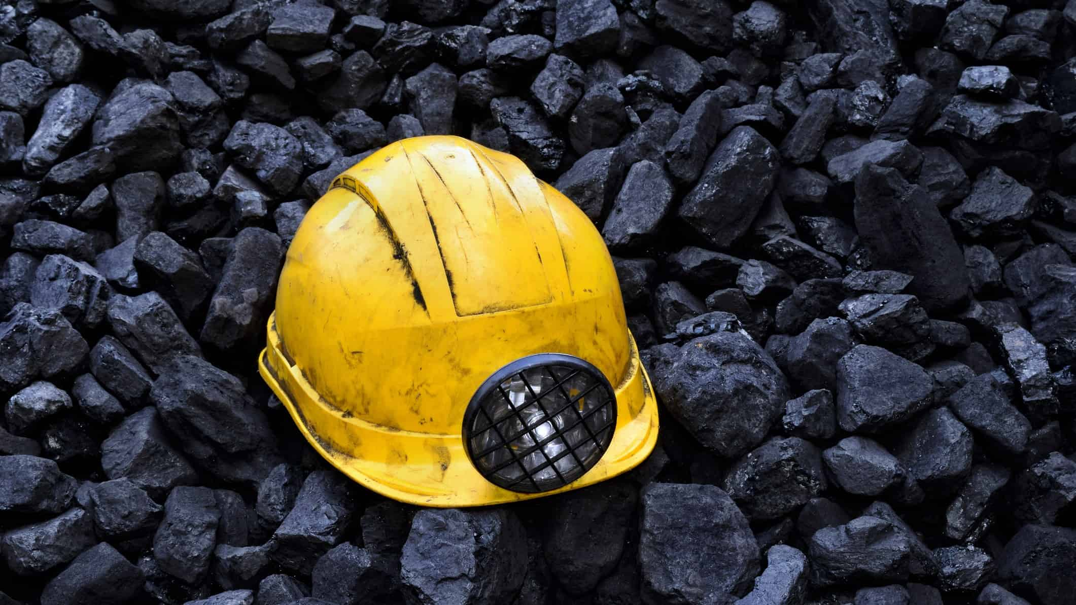 mining hat on lumps of coal representing mineral resources share price