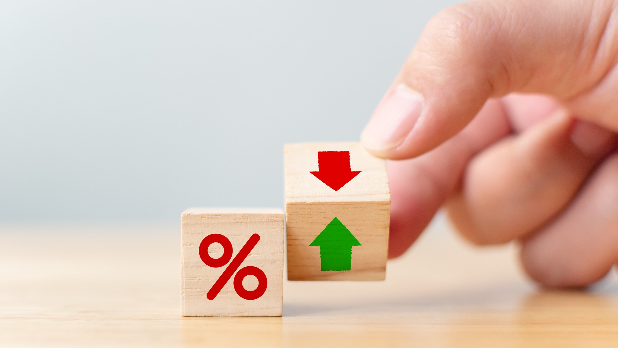A hand moves a building block from green arrow to red, indicating negative interest rates