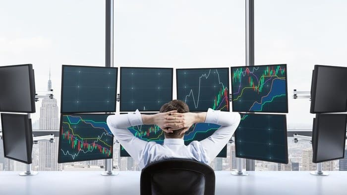 Investor sitting in front of multiple screens watching share prices