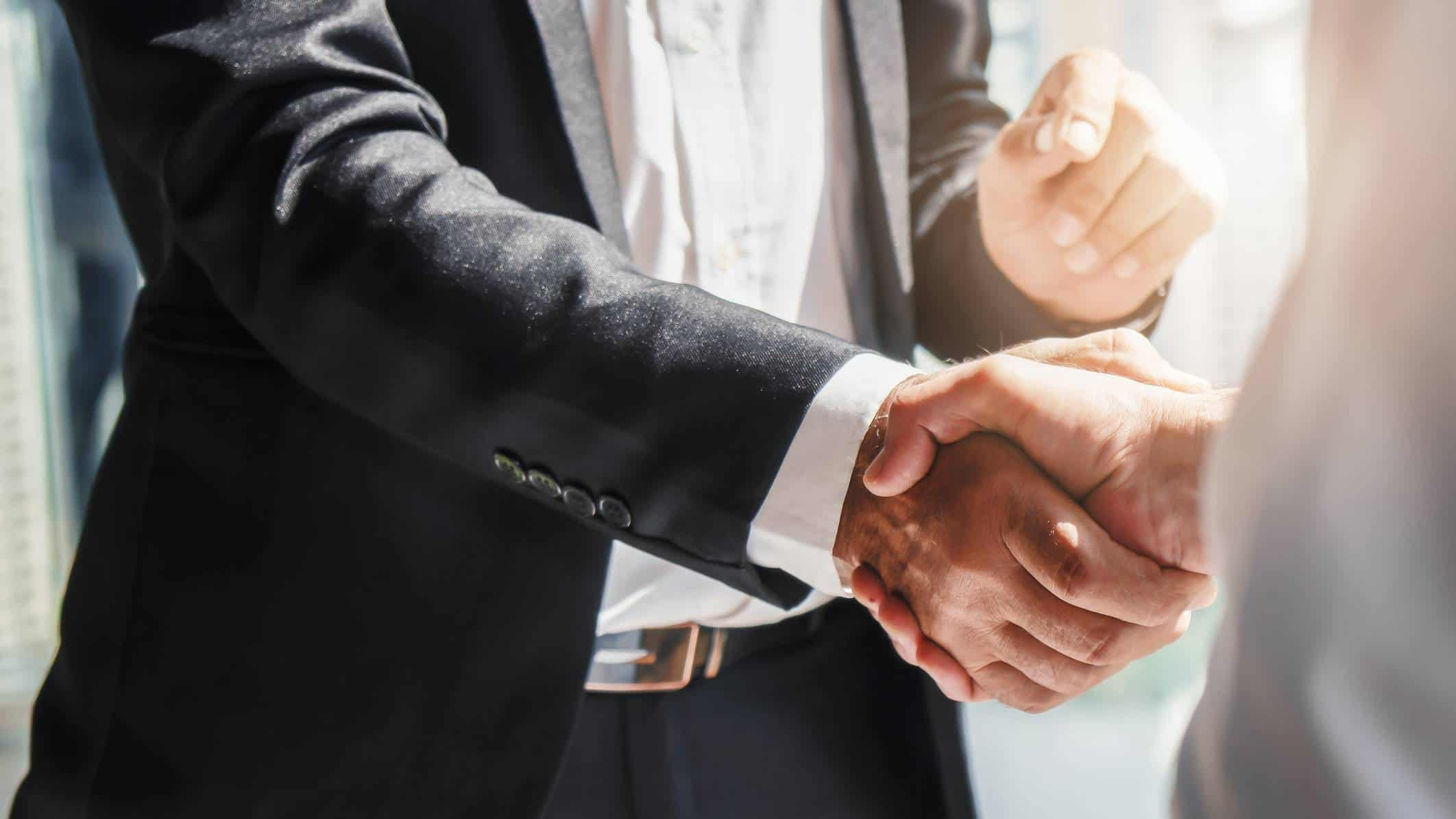 2 businessmen shaking hands, indicating a partnership deal and share price lift