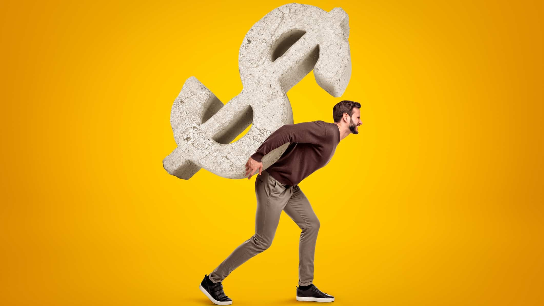 man carrying large dollar sign on his back representing high P/E ratio or dividend