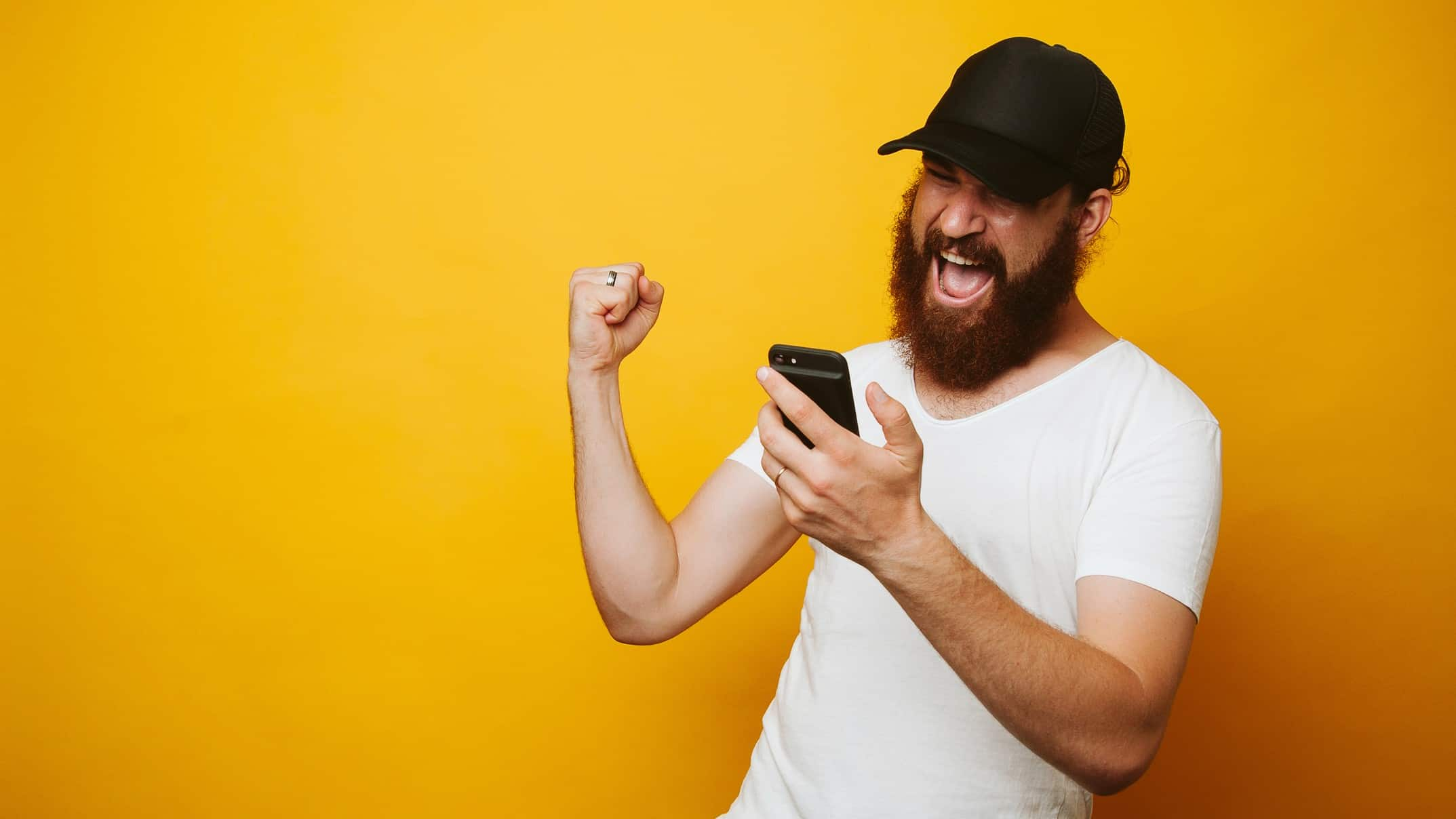 man looking at mobile phone and cheering representing surging pointsbet share price