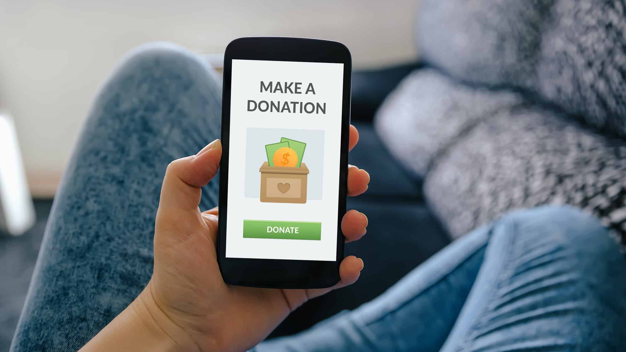 man holding mobile phone that says make donation