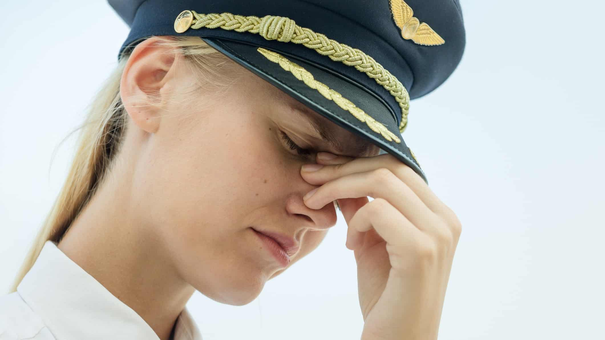 qantas pilot putting hands to her face as if distraught
