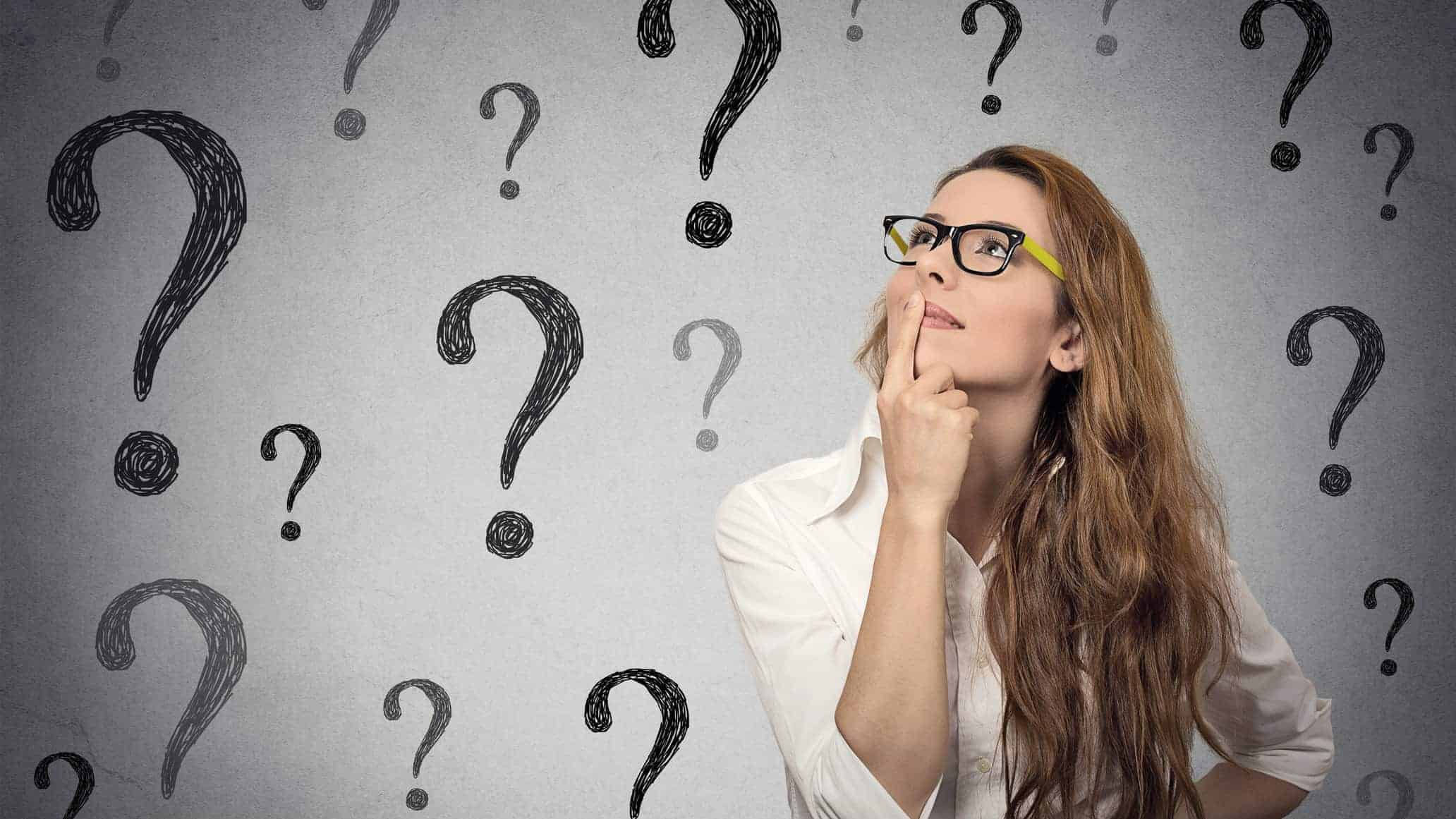 woman surrounded by question marks as if wondering about as share price