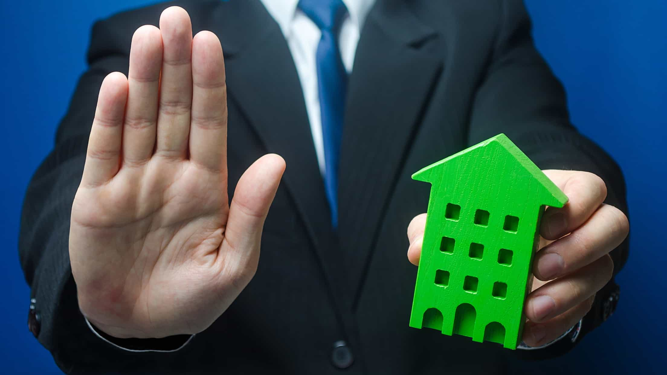 real estate investment trust trading halt represented by man holding hand up in stop motion and holding wooden block in the shape of a house