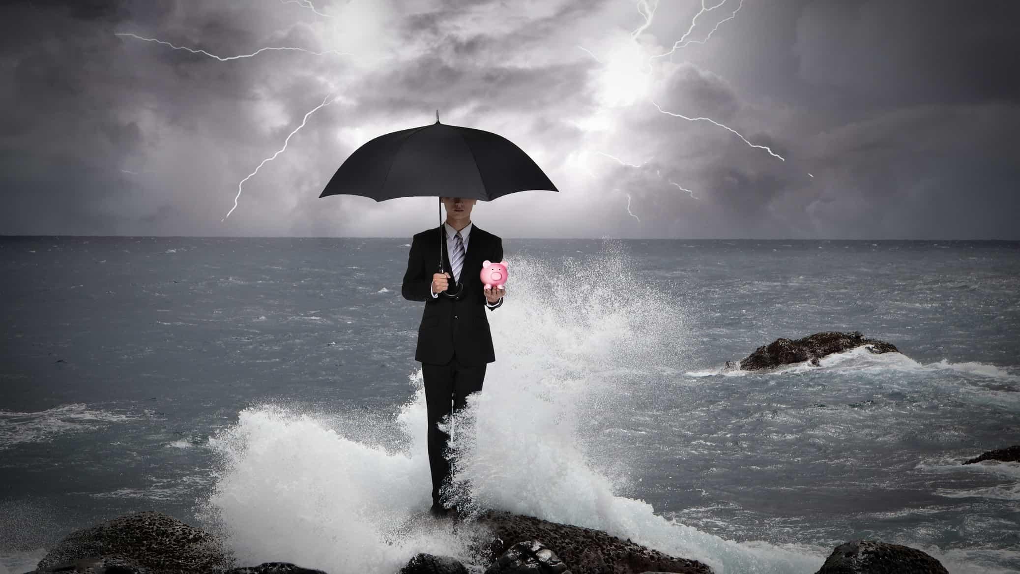 man holding piggy bank under umbrella during a storm